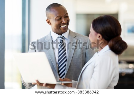 friendly african vehicle dealership principal and saleswoman working on laptop - stock photo