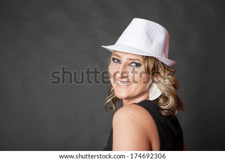 Friendly and happy young adult woman wearing white pinstripe hat - stock photo