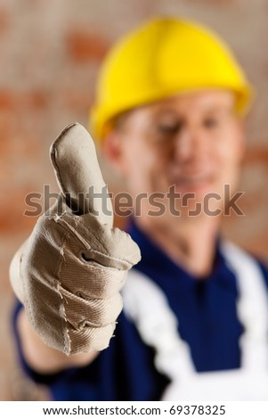 Friendly and reliable construction worker giving thumbs up, focus on thumb - stock photo