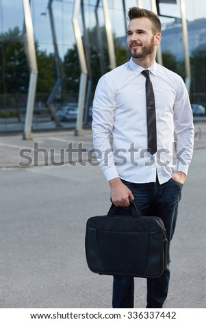 Friendly and smiling handsome businessman in front of building