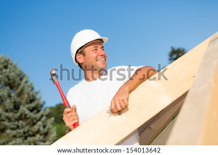 Friendly artisan working hard to build the roof of a new house - stock photo
