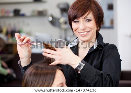 Friendly attractive hairstylist with a beautiful beaming smile cutting a womans hair in a professional hair salon - stock photo