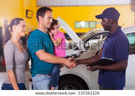 friendly auto mechanic handshaking with family inside workshop - stock photo