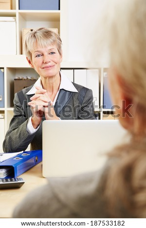 Friendly bank adviser listening to senior woman in her office - stock photo