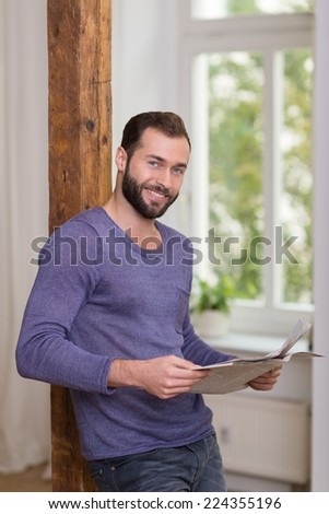 Friendly bearded man relaxing with a newspaper leaning against a vintage wooden door jamb looking at the camera with a happy smile - stock photo