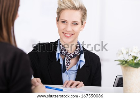 Friendly beautiful receptionist standing behind the counter assisting a guest to check into a hotel - stock photo