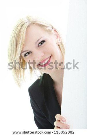 Friendly beautiful woman with a wide smile holding the side of a a blank white sign for your text - stock photo