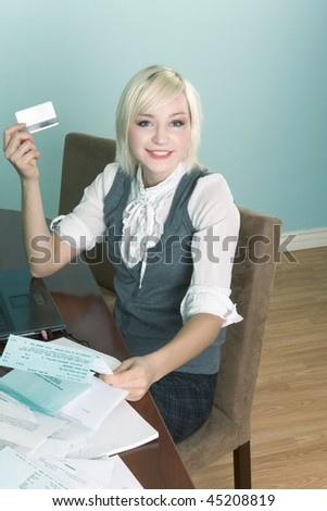 Friendly blond Caucasian female sting by table with laptop and holding creditcard preparing to pay her bills online