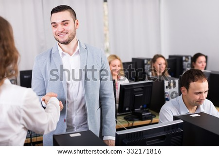 Friendly boss greeting new satisfied colleague at office - stock photo