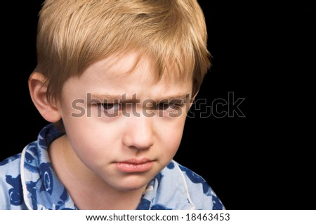 Friendly boy with a blue shirt against a black background - stock photo
