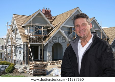 Friendly builder in front of home under construction. - stock photo
