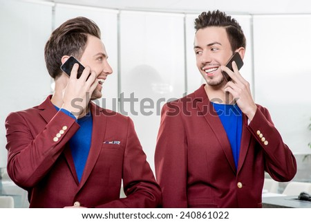 Friendly business brothers twins in red jackets using mobile phone in white office - stock photo