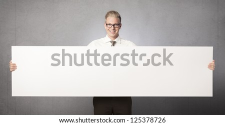 Friendly businessman holding white blank horizontal billboard with space for text isolated on grey background. - stock photo