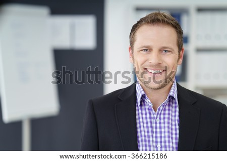Friendly businessman with a warm smile of welcome posing in the office, head and shoulders looking at the camera - stock photo