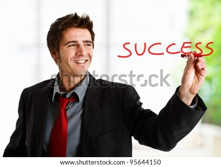 Friendly businessman writing the word Success on the screen - stock photo