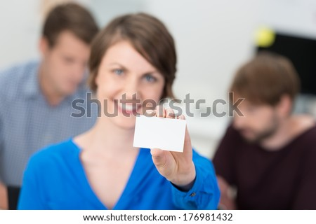 Friendly businesswoman holding up a blank card for your credentials or contact details with focus to the card - stock photo