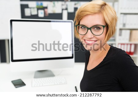 Friendly businesswoman working at her computer turning to give the camera a beaming smile with a blank computer monitor with copyspace behind her - stock photo
