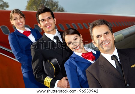 Friendly cabin crew smiling with an airplane at the background - stock photo