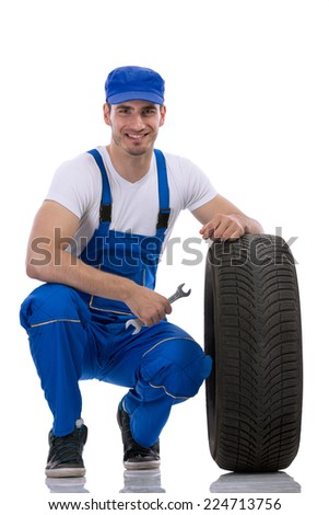 Friendly car mechanic with  tires and wrench - stock photo