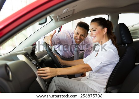 friendly car sales consultant showing a new car to young woman - stock photo
