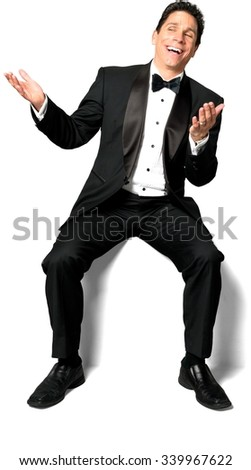 Friendly Caucasian man with short black hair in a tuxedo sitting and talking with hands - Isolated - stock photo