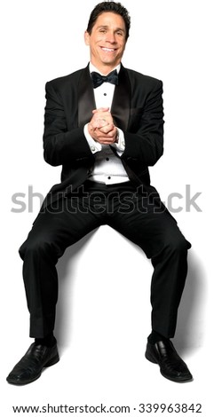 Friendly Caucasian man with short black hair in a tuxedo sitting with clasped hands - Isolated - stock photo
