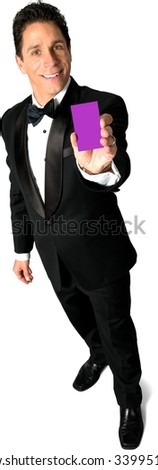 Friendly Caucasian man with short black hair in evening outfit holding business card - Isolated - stock photo