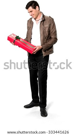 Friendly Caucasian man with short dark brown hair in casual outfit holding wrapped gift - Isolated