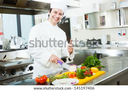 Friendly chef preparing vegetables in his kitchen - stock photo