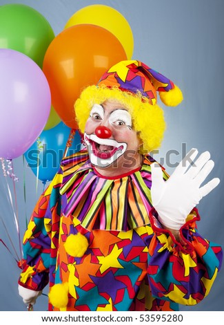 Friendly circus clown holding a bunch of balloons and waving hello. - stock photo