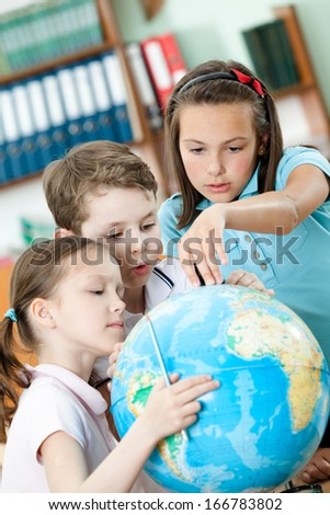 Friendly classmates help to each other to find something at the terrestrial globe. Schooling process - stock photo