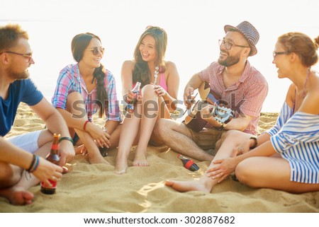 Friendly company with drinks relaxing on sand - stock photo