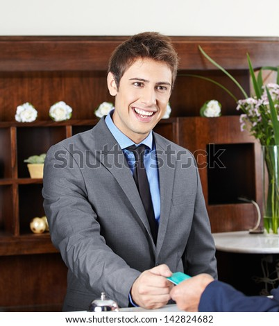 Friendly concierge working at check-in counter in hotel - stock photo