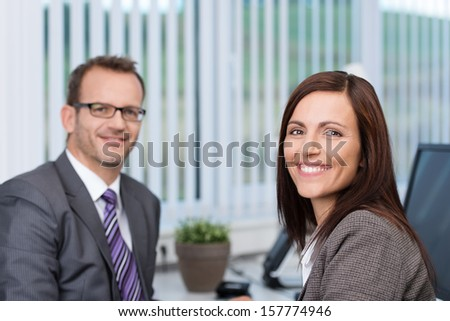 Friendly confident businesswoman with a lovely motivated smile sitting in her office with a male colleague - stock photo