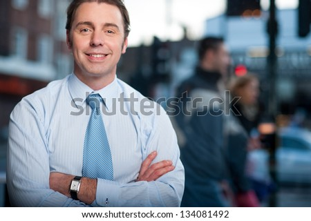 Friendly corporate guy posing with arms crossed. Street background. - stock photo