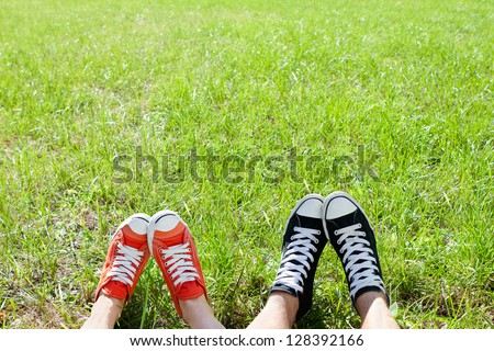 Friendly couple in sneackers in green grass - stock photo