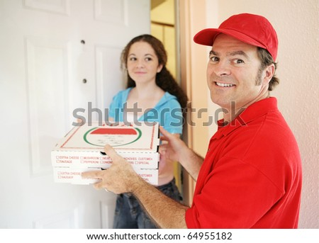 Friendly delivery man handing pizza to a customer. - stock photo