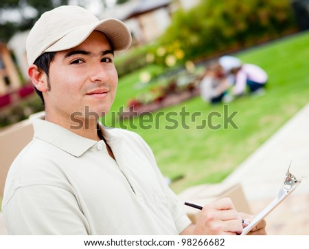 Friendly delivery man holding a clipboard outdoors - stock photo