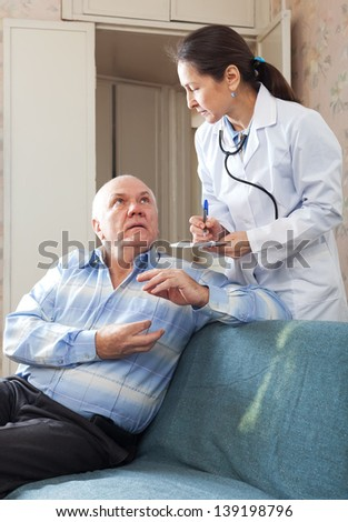 Friendly doctor asked senior patient feels - stock photo
