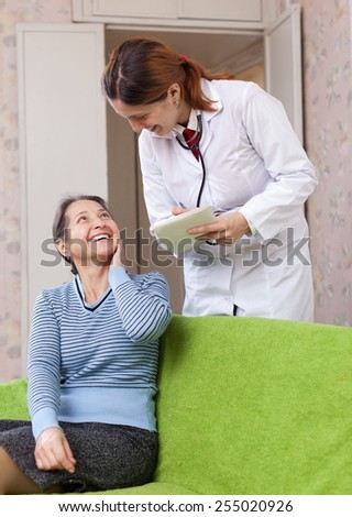 friendly doctor asks mature patient feels at medical hospital - stock photo