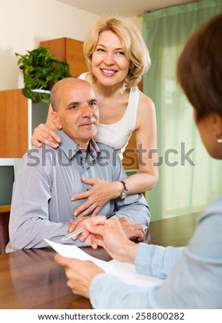 Friendly elderly  couple discussing details of private insurance with agent
