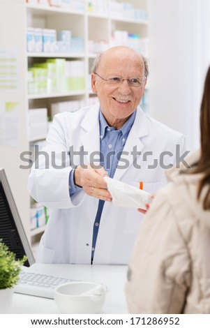 Friendly elderly male pharmacist standing behind the counter in the pharmacy dispensing prescription medicine to a patient with a smile - stock photo