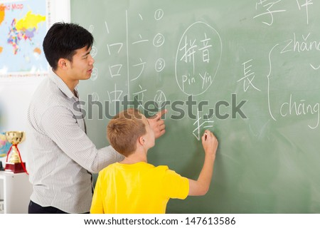 friendly elementary school teacher helping young boy writing chinese on chalkboard - stock photo