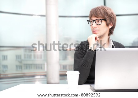 Friendly executive sitting in front of laptop in his office. Big window at the background. Looking away, daydreaming