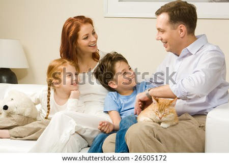 Friendly family members sitting on comfortable sofa and communicating at home - stock photo