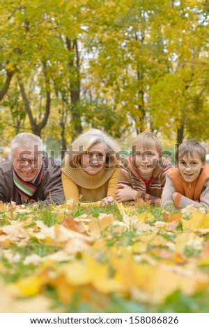 friendly family walking in the park in autumn together