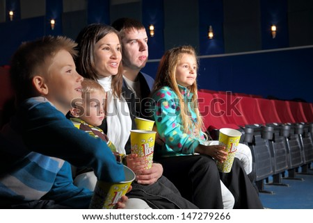 Friendly family with interest watching a movie and eating popcorn in the cinema