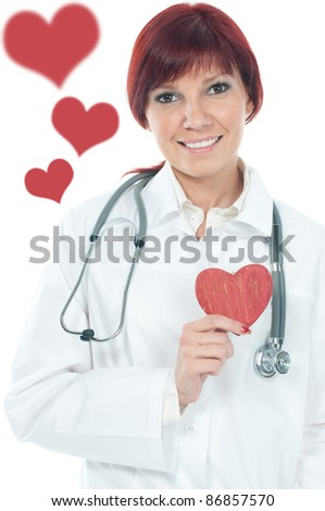 Friendly female cardiologist smiling and holding a small wooden heart - stock photo