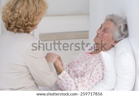 Friendly female doctor comforting a senior patient at hospital or retirement house - stock photo