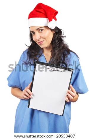 Friendly female doctor in blue scrubs with christmas hat, holding the blank clipboard on white background - stock photo